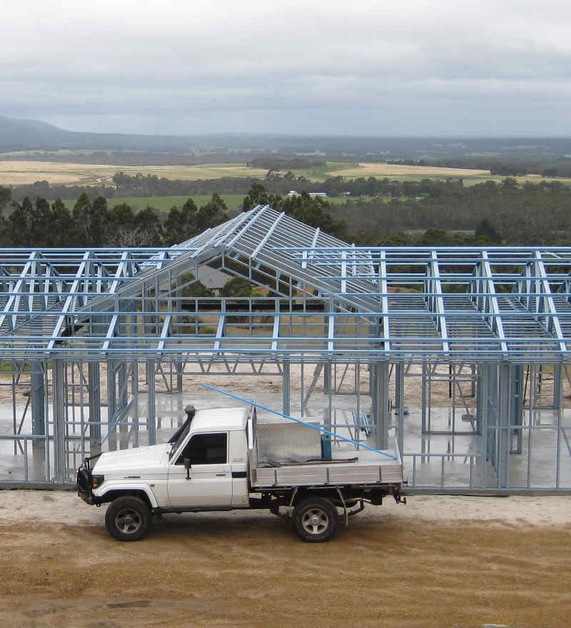 The CCS ute in front of a steel frame house being built.