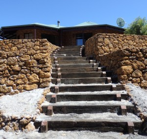 A coffee rock wall with a stair through the middle made with railway sleepers.